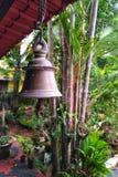 Υπαίθριο ινδικό κουδούνι χαλκού που κρεμά τον κόκκινο κήπο φοινικών στοκ φωτογραφία