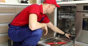 Υπηρεσία συντήρησης εγχώριων συσκευών - επισκευαστής που εργάζεται με το πλυντήριο πιάτων φιλμ μικρού μήκους