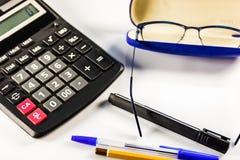 Υπολογιστής, γυαλιά, στυλοί και μολύβι στον άσπρο πίνακα στοκ εικόνες
