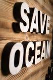 ΩΚΕΆΝΙΕΣ λέξεις SAVE που γίνονται με τις δομικές μονάδες που βρίσκονται στον ξύλινο πίνακα στοκ εικόνα με δικαίωμα ελεύθερης χρήσης