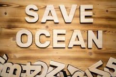ΩΚΕΆΝΙΕΣ λέξεις SAVE που γίνονται με τις δομικές μονάδες που βρίσκονται στον ξύλινο πίνακα στοκ φωτογραφίες