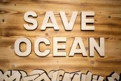 ΩΚΕΆΝΙΕΣ λέξεις SAVE που γίνονται με τις δομικές μονάδες που βρίσκονται στον ξύλινο πίνακα στοκ φωτογραφία