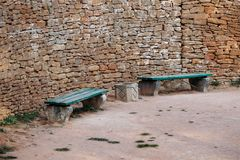 Πάγκος κοντά στον αρχαίο τοίχο που στρώνεται με τα τούβλα στο πάρκο στοκ φωτογραφία