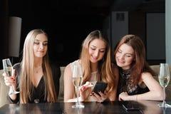 Πάντα συνδεμένος, εθισμός Διαδικτύου, νέα κορίτσια στον καφέ που εξετάζει τα smartphones τους, κοινωνική έννοια δικτύων στοκ εικόνες
