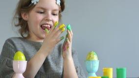 Πάσχα ευτυχές Το κορίτσι σύρει με τα δάχτυλά της, χρωματίζει τα αυγά Πάσχας Κίτρινα λερωμένα χέρια απόθεμα βίντεο