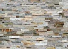 Πέτρινος τοίχος φιαγμένος από ριγωτές συσσωρευμένες πλάκες των φυσικών βράχων Επένδυση για τα εξωτερικά, στοκ φωτογραφία
