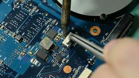 Πίνακας κυκλωμάτων υπολογιστών επισκευής: συγκολλώντας συνδετήρας στη μητρική κάρτα lap-top απόθεμα βίντεο