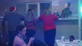 Πίσω άποψη τεσσάρων νεαρών άνδρων που πίνουν την μπύρα και που μιλούν καθμένος στο μετρητή φραγμών απόθεμα βίντεο
