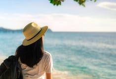 Πίσω άποψη της ευτυχούς νέας ασιατικής γυναίκας στην περιστασιακή μόδα ύφους με το καπέλο αχύρου και το σακίδιο πλάτης Χαλαρώστε  στοκ εικόνα με δικαίωμα ελεύθερης χρήσης