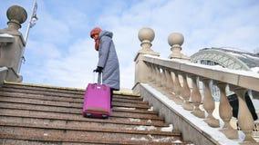 Πίσω άποψη του νέου ενήλικου κοριτσιού στο θερμό παλτό και το ζωηρόχρωμο πλεκτό καπέλο και scaft την αναρρίχηση επάνω από τα σκαλ φιλμ μικρού μήκους