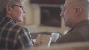 Πίσω του ζεύγους, του ηληκιωμένου και της γυναίκας, που κάθονται στον καναπέ με ένα βιβλίο και που μιλούν και που χαμογελούν ο έν απόθεμα βίντεο
