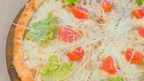 Πίτσα με το κοτόπουλο και το τυρί, ντομάτες και μαρούλι στην κορυφή στον ξύλινο πίνακα απόθεμα βίντεο