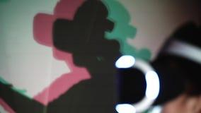 Παίζοντας κορίτσι άποψης λεπτομέρειας στην κάσκα VR με τη χρωματισμένη σκιά απόθεμα βίντεο