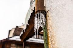 Παγωμένο νερό που ρέει από τη στέγη μέσω μιας χαλασμένης, σκουριασμένης, υδρορροής μετάλλων που είναι στην πρόσοψη του κτηρίου στοκ εικόνα