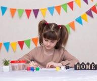 Παιδί που κάνει τη σπιτική ευχετήρια κάρτα Το μικρό κορίτσι χρωματίζει την καρδιά στη σπιτική ευχετήρια κάρτα ως δώρο για την ημέ στοκ φωτογραφίες