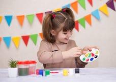 Παιδί που κάνει τη σπιτική ευχετήρια κάρτα Το μικρό κορίτσι χρωματίζει την καρδιά στη σπιτική ευχετήρια κάρτα ως δώρο για την ημέ στοκ εικόνες