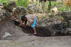 Παιδί που σκάβει μια τρύπα στοκ φωτογραφία