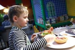 Παιδί που τρώει burger στοκ φωτογραφία