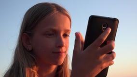 Παιδί που παίζει Smartphone, παιδί στην παραλία στο ηλιοβασίλεμα, κορίτσι χρησιμοποιώντας την ταμπλέτα στην ακτή απόθεμα βίντεο