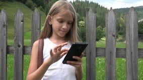 Παιδί που παίζει Smartphone υπαίθριο, παιδί στην ταμπλέτα, χαλάρωση κοριτσιών στη φύση απόθεμα βίντεο