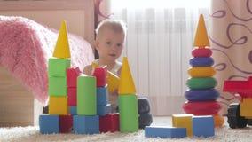 Παιχνίδι αγοριών παιδιών με τις δομικές μονάδες που κάθονται στο πάτωμα στο σπίτι Παιδικό παιχνίδι στο πάτωμα με τα εκπαιδευτικά  φιλμ μικρού μήκους