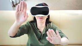 Παιχνίδι γυναικών στο παιχνίδι σχετικά με κάτι με το χέρι που φορούν τα σύγχρονα γυαλιά εικονικής πραγματικότητας φιλμ μικρού μήκους