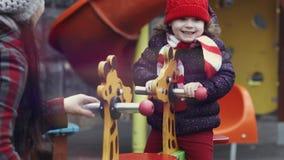 Παιχνίδι μητέρων με την ευτυχή ηλικία 3-4 κοριτσιών γέλιού της στα θερμά ενδύματα rocker στη φωτεινή ζωηρόχρωμη παιδική χαρά απόθεμα βίντεο