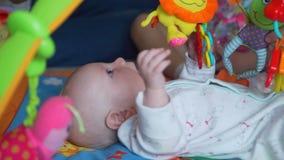 Παιχνίδι μωρών με τα παιχνίδια στο χαλί φιλμ μικρού μήκους