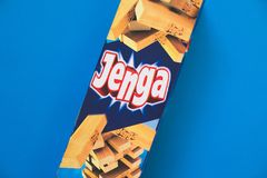 Παιχνίδι πύργων Jenga - ξύλινοι φραγμοί στο μπλε υπόβαθρο στοκ φωτογραφίες