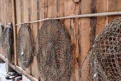 Παλαιά δίχτυα του ψαρέματος που κρεμούν στον ξύλινο τοίχο στοκ φωτογραφίες