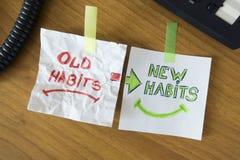 Παλαιές συνήθειες και νέες συνήθειες χειρόγραφες στα άσπρα κομμάτια χαρτί στο γραφείο στοκ φωτογραφία