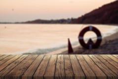 Παλαιός ξύλινος πίνακας για τη διαφήμιση των προϊόντων σας, ξύλινος πίνακας ενάντια στη θάλασσα στο ηλιοβασίλεμα στοκ φωτογραφίες