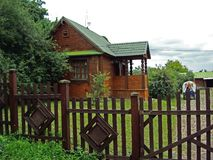Παλαιό ξύλινο σπίτι με την πράσινη στέγη και τον καφετή φράκτη στοκ φωτογραφία με δικαίωμα ελεύθερης χρήσης