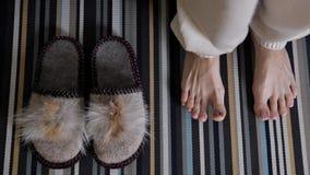 Παντόφλες στον τάπητα Το κορίτσι βάζει στα εγχώρια παπούτσια Η άνεση, θερμαίνει απόθεμα βίντεο