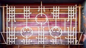 Παράθυρο με τα ζωηρόχρωμα ξύλινα παραθυρόφυλλα και άσπροι φραγμοί με το αρχικό σχέδιο στοκ φωτογραφία