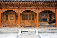 Παραδοσιακή ξύλινη κινεζική αρχιτεκτονική του σπιτιού και ενός ατόμου συνεδρίασης στοκ φωτογραφία