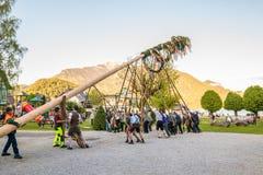 Παραδοσιακός που διακοσμείται maypole δημιουργείται κατά τη διάρκεια του λαϊκού φεστιβάλ στο αυστριακό αλπικό χωριό StGilgen σε W στοκ φωτογραφίες