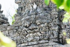 Παραδοσιακό τρομακτικό να φανεί γλυπτό πετρών νησιών του Μπαλί στον αρχαίο τοίχο στοκ φωτογραφία