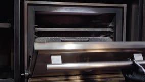 Παραδώστε τα μαύρα γάντια ανοίγει μια πόρτα ενός επαγγελματικού φούρνου ξυλάνθρακα για το ψήσιμο στη σχάρα απόθεμα βίντεο