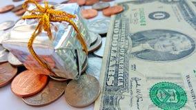 Παρόν κιβώτιο με τα αμερικανικά νομίσματα με το αμερικανικό υπόβαθρο δολαρίων στοκ εικόνες