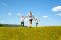 Πατέρας με δύο μικρά παιδιά που τρέχουν χέρι-χέρι στον πράσινο τομέα σε ένα υπόβαθρο του μπλε ουρανού και των σύννεφων Πατρότητα  στοκ φωτογραφία με δικαίωμα ελεύθερης χρήσης