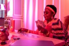 Παχουλός fortune-teller αφροαμερικάνων στα εθνικά στολισμούς που εξετάζει τις κάρτες στον πίνακα στοκ φωτογραφία με δικαίωμα ελεύθερης χρήσης
