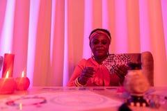 Παχουλός fortune-teller αφροαμερικάνων στα εθνικά στολισμούς που κάνουν την ανάγνωση Tarot στοκ εικόνα με δικαίωμα ελεύθερης χρήσης