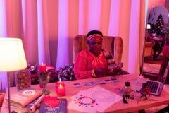 Παχουλός fortune-teller αφροαμερικάνων στα εθνικά στολισμούς που διαβάζει τις κάρτες Tarot στοκ φωτογραφία με δικαίωμα ελεύθερης χρήσης