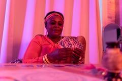 Παχουλός fortune-teller αφροαμερικάνων στα εθνικά στολισμούς που φαίνεται ενδιαφερόμενος στοκ φωτογραφία