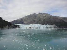 Παχύς παγετώνας μεταξύ δύο βουνών που γλιστρούν αργά στο Ειρηνικό Ωκεανό με ένα νεφελώδες σκηνικό στοκ φωτογραφίες με δικαίωμα ελεύθερης χρήσης