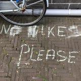 Πεζοδρόμιο με τις επιστολές κιμωλίας που δεν διαβάζουν κανένα ποδήλατο παρακαλώ και ένα σταθμευμένο ποδήλατο στοκ φωτογραφίες με δικαίωμα ελεύθερης χρήσης