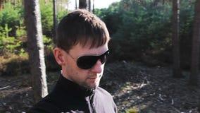 Περίπατος νεαρών άνδρων στο δάσος με τα γυαλιά ηλίου, μόνη μαγνητοσκόπηση απόθεμα βίντεο