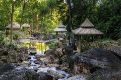 Περίπτερα για τη χαλάρωση με τις γέφυρες στις τράπεζες ενός ρεύματος βουνών με τις πέτρες στο τροπικό δάσος στοκ εικόνα