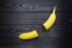 Περικοπή στη μισή μπανάνα στο σκοτεινό ξύλινο υπόβαθρο στοκ εικόνα με δικαίωμα ελεύθερης χρήσης